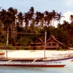 """Philippines - Boracay - """"Banca"""" outrigger canoes on beach with bungalow cabins behind"""